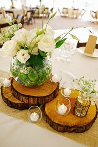 rustic wood stump and white flowers wedding centerpiece / http://www.deerpearlflowers.com/unique-wedding-centerpiece-ideas/2/