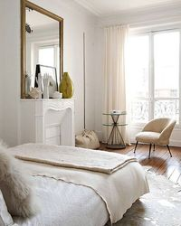 Serene and spare all-white Parisian bedroom style.