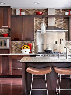 Tile Showstopper: A wall-to-wall glass tile treatment and tall stainless steel backsplash/range hood create an eye-catching centerpiece in this modern kitchen!