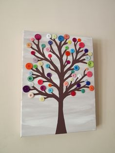 Paint the canvas with acrylic paint in alternating light and dark strips of gray then blend together. (Vary the width of the stripes for added interest. Paint on a simple brown tree and let dry. Glue on multicolored buttons. Very cute for a kid's room, classroom (teacher present idea!!!), hall or bathroom! Kids can help with this one too!