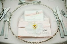 Blush colored napkin with orchid adornment