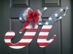 """Wooden Door Hanger Patriotic H - Made of 1/2"""" thick wood, this letter is painted red, white and blue with a clear satin sealer to be weather resistant in our """"Astoria"""" font. All of our letters are complete with hangers on the back and are ready to display wherever you like. $49.95"""