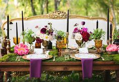Gorgeous rustic tablescape with moss, ferns and pops of purple