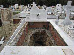 Exhumed grave in Greece. Due to lack of space, this is standard practice. To make room for newly deceased, the bodies are exhumed after 3 years and the bones placed in an ossuary with the bones of other members of the family, or, if there is no such box, they are simply buried in another part of the plot, perhaps even underneath one of the coffins.