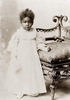 Full length portrait of an unidentified a young African American girl wearing a formal white princess gown with gloves. Daniel  Murray, photographer. 1899