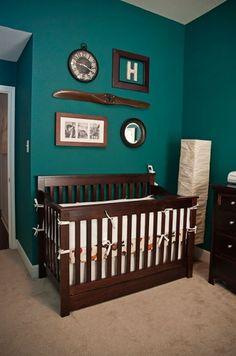Dark teal walls with mahogany crib