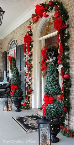 Christmas Front Door. Outdoor Decorating. Topiaries  in Urns, Red Ribbon  & Ball Ornaments with Snowflakes from Our Southern Home Christmas Tour 2013