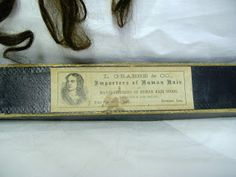 """1850s/60s Curls These 3 curls measure approx. 11, 12, and 13"""" long, is dark brown. 2 of the curls have wired bands at the top, the other has a small loop. The label on the box reads """"L Grabbe & Co, Importers of Human Hair and Manufacturers Of Human Hair Goods, Wholesale and Retail, Under First National Bank, Davenport, Iowa"""". The box in skewed out of shape and the top is missing one end flap."""