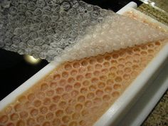 Prudent Lou: Bubble wrap on top of soap mold to make a faux honeycomb look. Also, PVC pipe for a cheap soap mold.