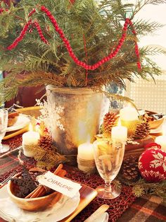 Forget the Florist: Trim evergreen branches from your yard or an obliging neighbor's tree to serve as a centerpiece. Place fresh boughs in a galvanized bucket and swag a wooden bead garland around the greens. Use leftover Christmas tree clippings to fill in the base of the tablescape. holiday, table settings, christmas table decorations, rustic charm, christmas centerpieces, christmas tables, christmas decorations, decorating ideas, rustic christmas