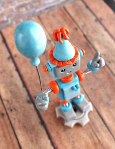 """Robot 1st Birthday Cake Topper in blue and orange.  Requested details: little bot robot holding a balloon and one finger up representing his first birthday. He stands on a silver gear with the boy's name letter-pressed into the bottom make it an awesome keepsake. Approximately 4"""" inches in height. Robot sculptures combining polymer clay, wire woven into coil springs, varnish and (sometimes a little heart) handmade by HerArtSheLoves. theawesomerobots.com"""