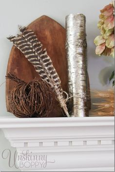 Metallic birch log with turkey feathers and a grapevine pumpkin- great for fall mantel decor