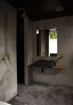 love this concrete style bathroom with brass taps.