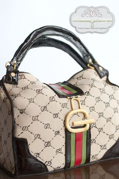 A Gucci handbag cake. Hand painted fondant canvas with chocolate fondant double handles and trim.