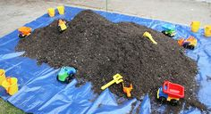 A bunch of dirt on a tarp with plastic bugs and such in it with shovels and trucks! Or in kiddy pool would be fun too.