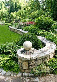 This stone scroll ends in a shade garden of solomon seal, strawberry begonias, lonicera, Japanese painted ferns, and more.  A Planters design.  Atlanta, GA