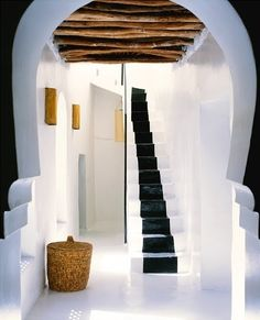 What a great Moorish arch leading to a staircase with a black runner painted onto the white stairs.  Like! http://cococozy.com