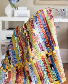 This quilt pattern featured in Quilty September/October 2013 features juicy fabric color strips and squares that come together to create a stunning quilt. Rich gold, royal blue, and rusty red stripes. Take a trip. Quilt by Pamela Goecke Dinndorf.