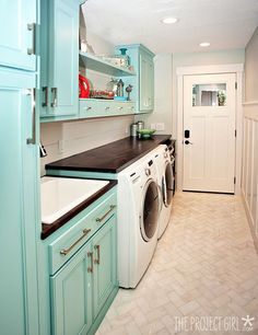 Laundry room: Fun aqua cabinets, wood counter and herringbone marble floor.