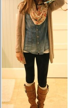 Brown cardigan over a jean button up shirt. A floral scarf, black jeans, and knee length tan boots.
