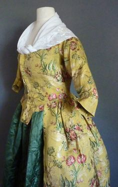 Robe a la Polonaise, Silk 1760's; Dress 1775-80. Bright yellow ribbed silk with 3 graduated trees growing from a rocky hillock, large roses on extended stems, one group in pink the other magenta, an old knarled tree entwined with green flowerheads with roses at the base, all in shades of deep pink, magenta, mid & dark green, brown & yellow, with silver coloured silks in the background, the back bodice boned from 4 in or 10 cm down &  pointed into the skirt, the bodice lined with linen.