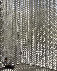 Twenty-thousand pieces of aluminium form a chain-mail blanket over this concrete performance venue