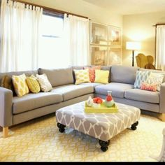 """Grey and yellow living room. Love the oversize ottoman used as a """"coffee"""" table!"""