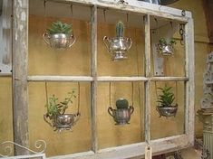 Old window with hanging silver pots as planters