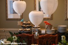 DIY homemade hot air balloon baby shower  decorations made from paper lanterns with toy animals in the basket