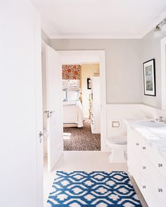 Bathroom - A patterned blue rug in a bathroom with light-gray walls