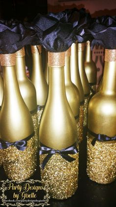 DIY Black & Gold Centerpieces Spray painted wine bottles. Mod Podge bottom half and sprinkle glitter; some ribbon and a flower