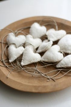 white felt hearts in a wooden bowl.