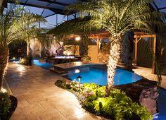 Night view - swimming pool, stone walls, travertine decking and bridge, pergola, stone spa, stone grotto waterfall