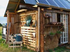 Farm/Garden Tool Storage Idea: upcycle a wood pallet to store tools upright.  (We also love how this garden shed has solar panels on it!)