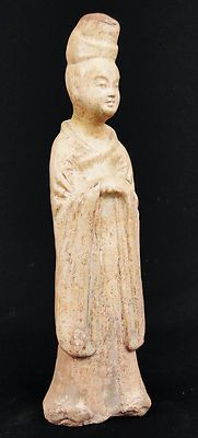 "Antique Chinese Tang Dynasty Pottery Court Lady Figure (C. 6-9th C. AD)  Description : A circa 6-9th Century Tang Dynasty pottery figure of a court lady. She is standing with serene expression, her hair tied high in ornamentation, wearing a robe which shows if folds as it drapes over her arms. She has a creamy yellow spotted glaze.   Size : 8 1/4"" tall   Age : Tang Dynasty"