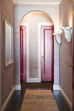 Tour a Cheerful and Elegant Family Home in NYC // colorful area rug, red painted door, white sconce
