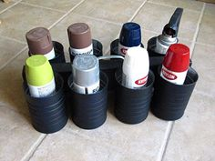 """coffee cans bolted to a center scrap of wood board:  great spray paint can holder. Pipe strap for a """"handle."""""""