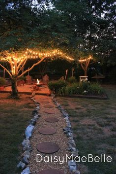 stone path leads to the firepit with surrounding anarondack  chairs, string lights and tiki torches