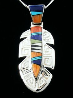 "Designed by Calvin Begay, Inlaid by a Navajo artist    Size: 2 1/8"" Tall w/bail, 3/4"" Wide    Stones: Turquoise, Spiny Oyster, Lapis and Black Jade    Signed Calvin Begay    Comes With Certificate of Authenticity"