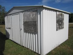 Windows are boarded because other shed was broken in to. Windows are in excellent condition! Nice shed 10X14ft. 7ft high in center. Wood workbench, wood flooring, windows with screens. No leaks! Must go!