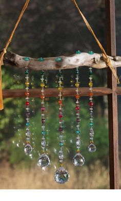 Driftwood branch strung with leather (chain might be better???) and bright reflective beads as #suncatcher - Fire Mountain Gems, designed by Mary Wertz, includes materials list - tå√
