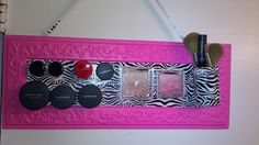 My homemade magnetic makeup holder. I got all the materials at Hobby Lobby!  MATERIALS:  Magnets,  Hot Glue Gun/Glue,  Zebra Duct Tape, Tin Name Board. HOW I MADE IT:  I first did two strips of the zebra tape for my background.  I then added one magnet to the back of each piece of makeup I wanted on my board.  Next I took an empty pill container and covered it with the zebra tape and added three magnets to the back.  Finally I placed all of them on the board:)