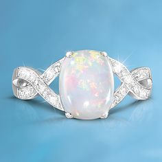 Solid sterling silver women's ring with oval-shaped Australian opal at its center and crisscrossed pavé ribbons of 12 genuine diamonds