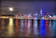 The water shimmers with light.  A full moon rises over Hong Kong and the South China Sea and burns through the clouds just after sunset. by Trey Ratcliff.