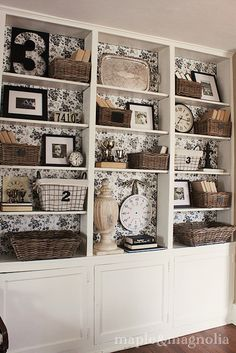 Line the back of the shelves with toile covered foam boards - easy to swap over when changing the decor