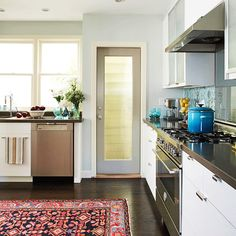 This kitchen has real style with the very modern cabinets combined with the traditional patterns of the backsplash and rug. I would love to have a lighted walk-in pantry! Or the blue ombre pot...