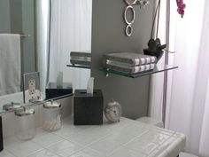 20 Stylish Bathroom Storage Ideas: Designer Erinn Valencich maximizes wall space by placing a floating shelf above the toilet. Small, clear canisters provide a stylish storage solution for toiletries, such as cotton swabs and cotton balls. From DIYnetwork.com