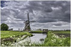 Sun and Clouds (clouds Spring sky water windmills ). Photo by henkhoekstra