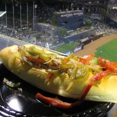 The San Diego Padres Sonoran Dog is a hearty roll stuffed with an all-beef hot dog spiraled with bacon is then topped with a choice of pinto beans, grilled onions and peppers, tomatoes, relish, tomatillo salsa, mayo, mustard, ketchup, and cheese.