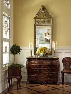 lovely gold antique mirror with a brown cabinet in a hallway